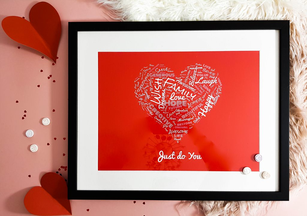 a framed picture of a heart of words